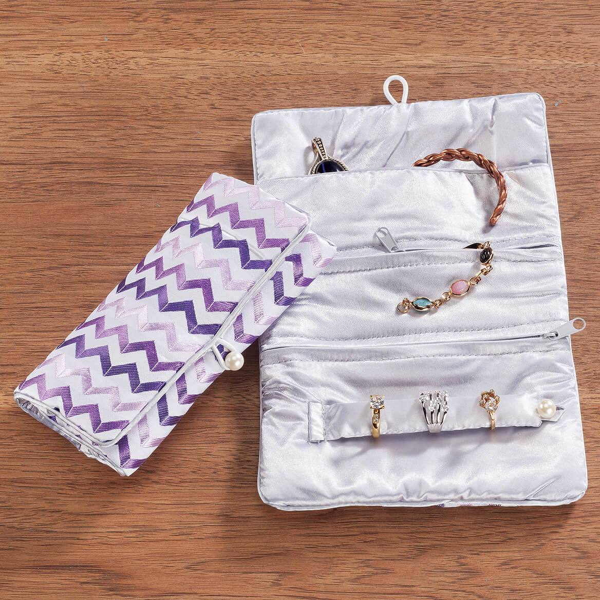 Zig Zag Purple Jewelry Roll A safe and stylish way to stash jewelry, this sateen tri-fold Zig Zag Purple Jewelry Roll keeps it organized with a fashionable chevron pattern and pearlesque button closure. Unroll the travel jewelry organizer to find a full-length compartment for necklaces and watches, 2 zip pockets to secure smaller items like bracelets and earrings, and a snap-close bar to keep rings safely organized. Perfect for home and travel! Jewelry roll measures 9 1/2  x 6 1/2  when opened, 6 1/2  x 3 1/2  rolled. A great value -- compare at $9.99-$14.99!