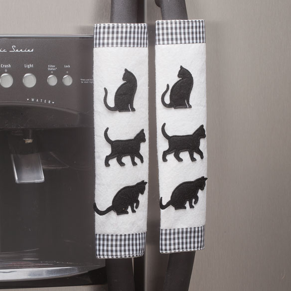 Cat Appliance Handle Covers - Set of 3 Add charming style and comfort to ordinary kitchen appliance handles with cat appliance handle covers. As practical as they are decorative, oven and fridge handle covers protect handles from fingerprints, grime and scratches. Simply slip around refrigerator and oven handles and secure with hook-and-loop closures. Pretty design features black cat silhouettes and gingham borders. 3-piece set; each 11 1/2 long x 7 1/2 wide. Polyester. Hand wash.