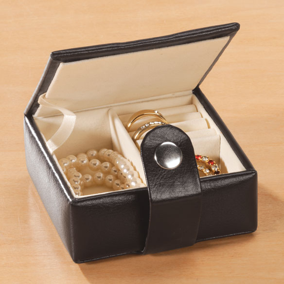 Mini Travel Jewelry Case Mini travel jewelry case is the perfect little travel companion. Black leather exterior features a cute stitched flower and silver snap. Inside you'll find 2 storage compartments and 3 ring slots to secure your favorite essentials on the go. At just 3 1/2  sq. and 1 1/2  H, this jewelry travel case keeps jewelry safely nearby in your purse or carry-on bag
